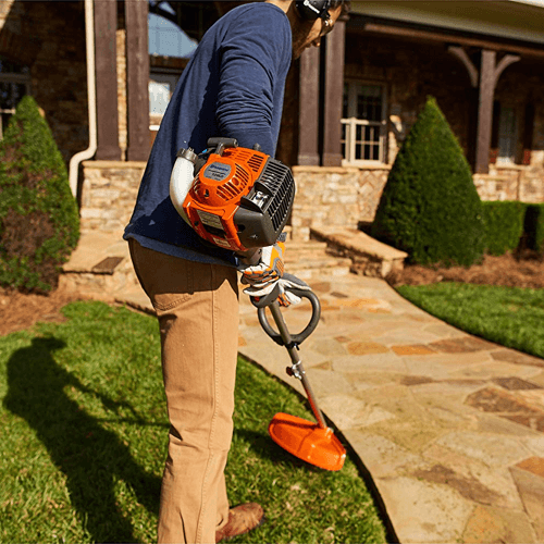 an image showing the Husqvarna 128ld 17-inch straight shaft detachable string trimmer being used
