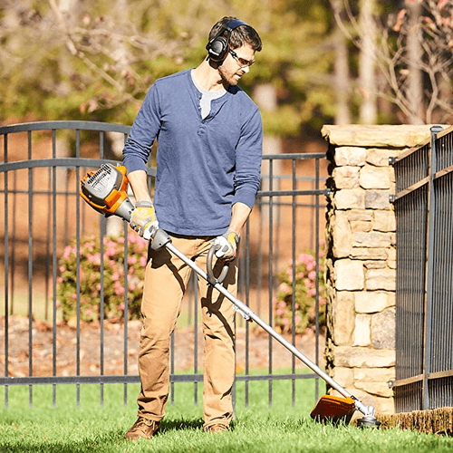 an image of the Husqvarna 128ld 17-inch straight shaft detachable string trimmer in use