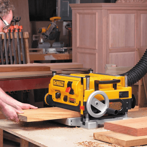 an image showing the dewalt dw735 wood planer planing a large piece of timber