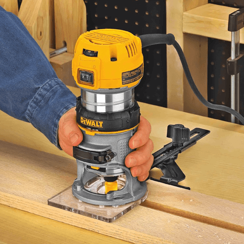 an image of the dewalt dwp611 compact router in use cutting a profile into wood
