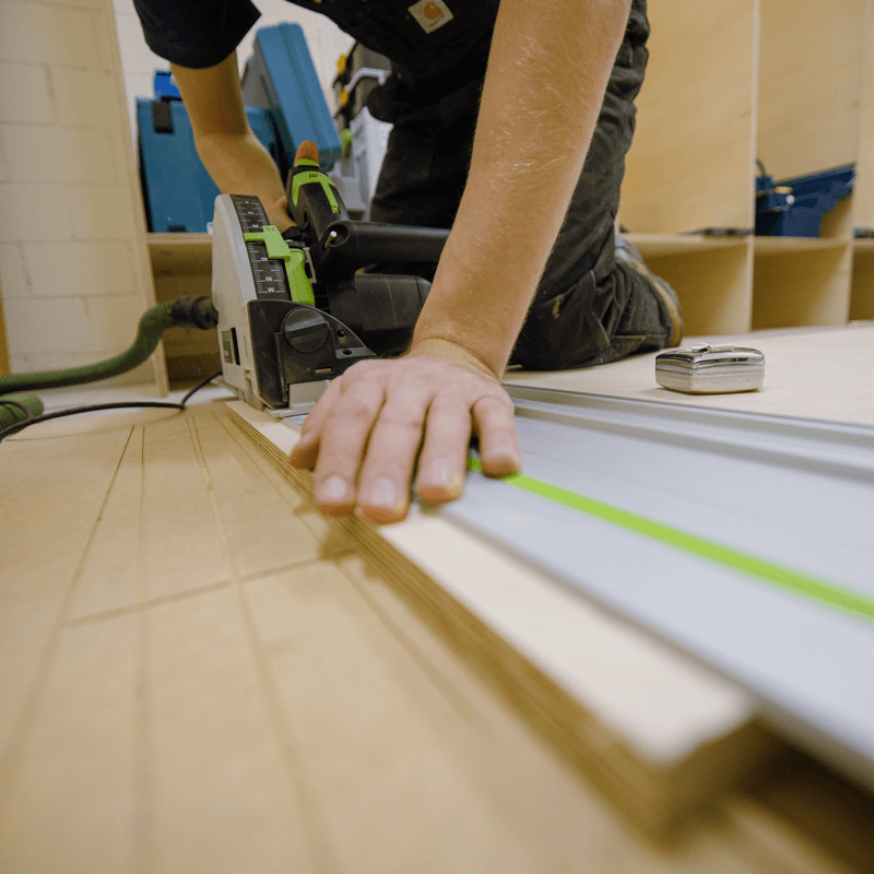 an image showing baltic birch plywood being cut with a track saw for use in a cabinet