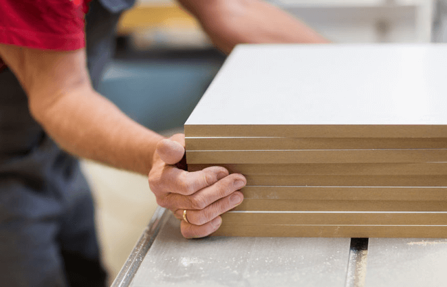 an image the edges of a stacked of mdf being flushed up to prevent damage from our how to stop mdf warping article