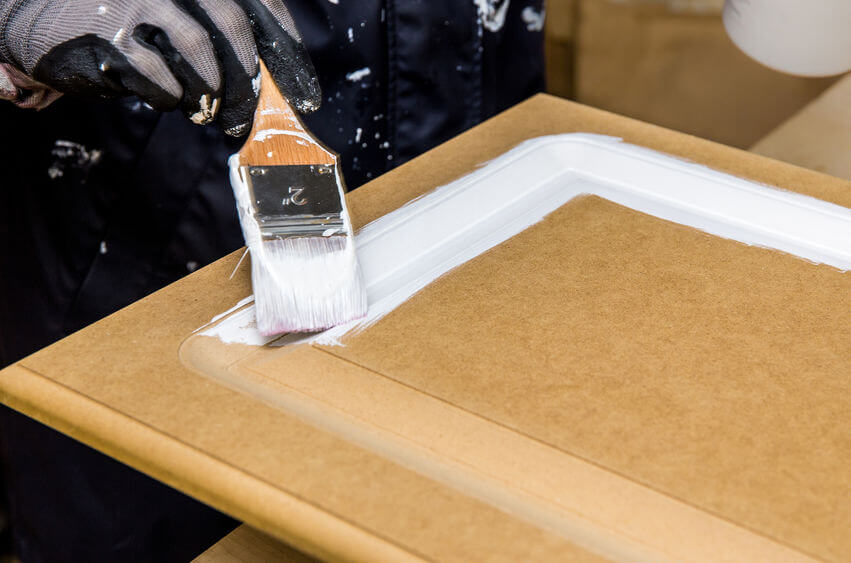 an image showing primer being applied to MDF using a brush