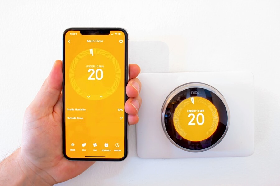 an image from an article about how the nest thermostat gets power showing the nest app being used on a smartphone