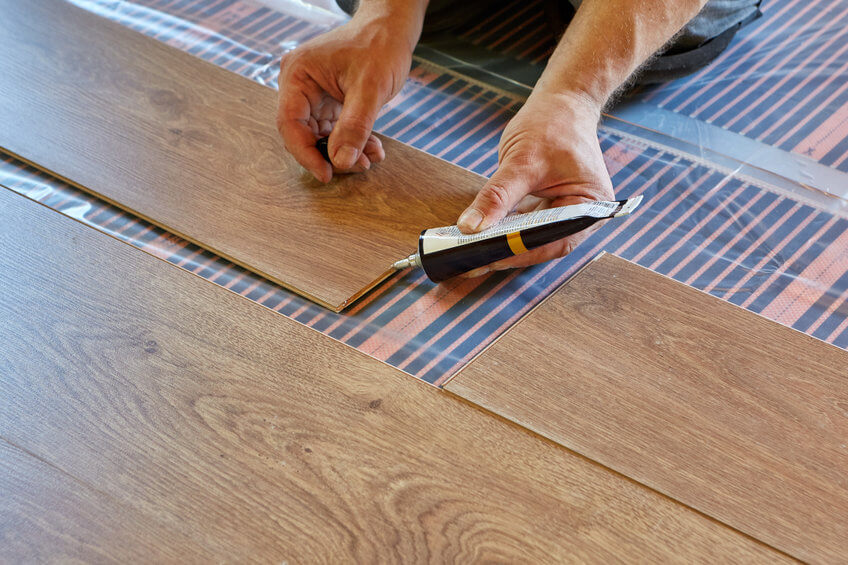 do laminate floors need to be sealed article image - an image showing sealant being applied to the joints on laminate flooring boards