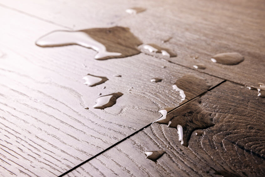 an image showing water on top of laminate flooring boards
